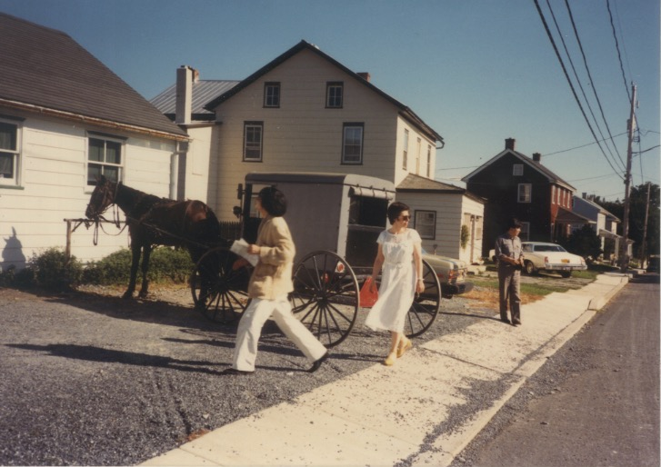 Madeline and Arakawa walking on a street near a horse drawn trailer (Sep 1986)
